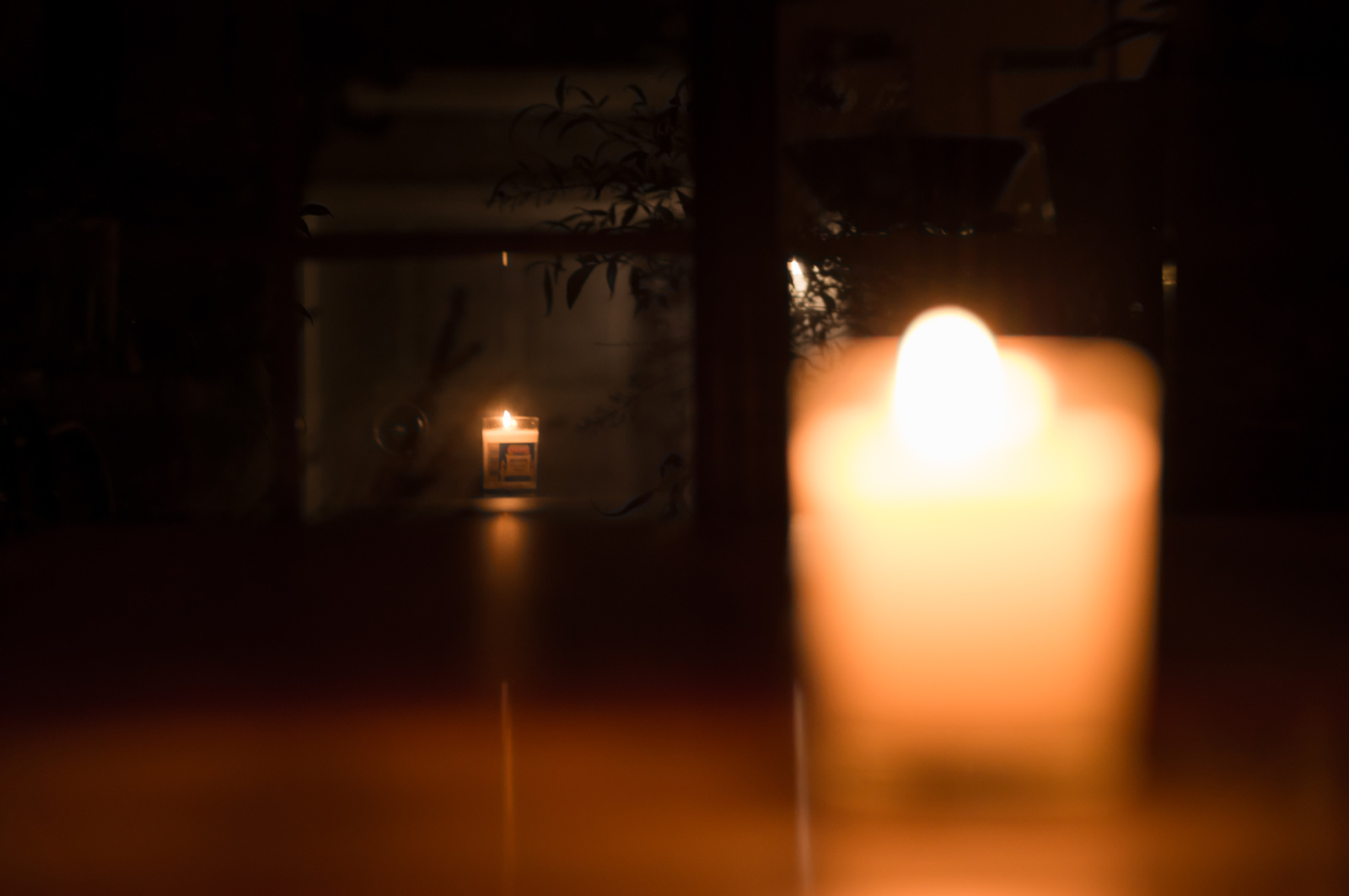 defocused candle in foreground, with reflection of candle in focus in the distance